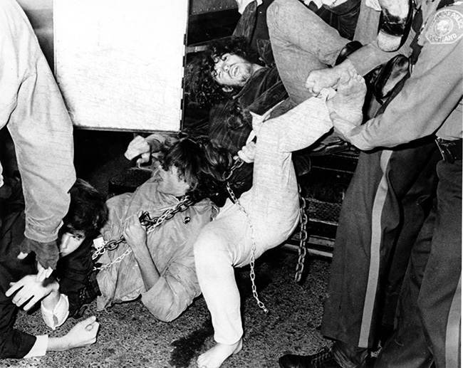 Six draft protesters are hauled into a police wagon after police cut them loose from the Selective Service office, where they had chained themselves in Portland, Ore., on Oct. 19, 1967. (AP Photos)
