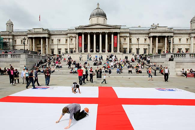 A man writes a message of support for the England football squad on a giant Saint George's Cross flag, in Trafalgar Square, central London ahead of the World Cup game against Algeria