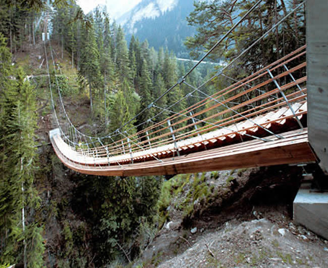 The bridge over the Traversinertobel, a side valley of the Via Mala, is the latest structure of this kind designed by engineer Jürg Conzett and his associate Rolf Bachofner . They solved the problem of connecting two different elevations over the gorge by creating a staircase. The staircase replaces a rope bridge for hikers that was wiped out by a rock slide. This suspended footbridge spans a distance of 56 metres, with a difference in height of 22 metres between the two ends. Read more at http://www.oddee.com/item_96882.aspx#TDkrZd2DksiWXxCw.99