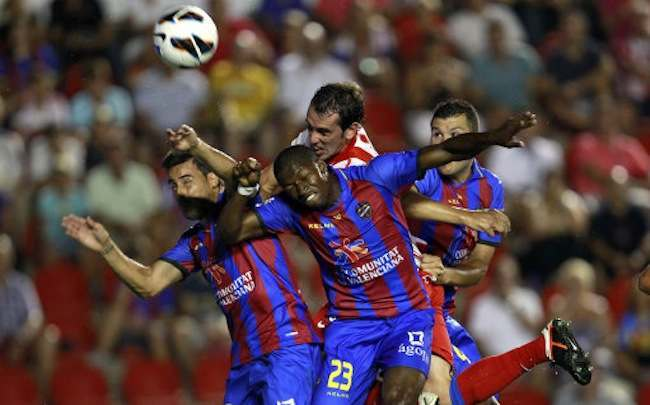 Atletico Madrid's Diego Godin from Uruguay, center background,  heads the ball next to Levante's Pedro Lopez, left, and Papa Diop from Senegal, right, during a Spanish La Liga soccer match at the Ciutat de Valencia stadium in Valencia, Spain, Sunday, Aug. 19, 2012. (AP Photo/Alberto Saiz)