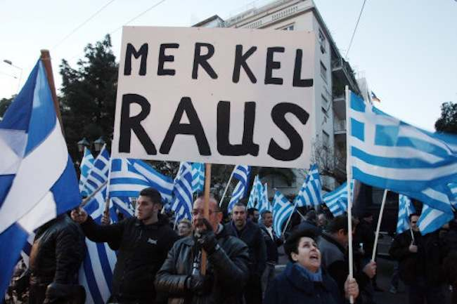 Supporters of the far-right party Golden Dawn hold up Greek flags and a sign that reads in German ''Merkel get out'' during a protest outside the Germany embassy in Athens on Friday, March 22, 2013. The party protested Germany's lead role in Cyprus' bailout crisis, as the island remains on the brink of bankruptcy. (AP Photo/Thanassis Stavrakis)
