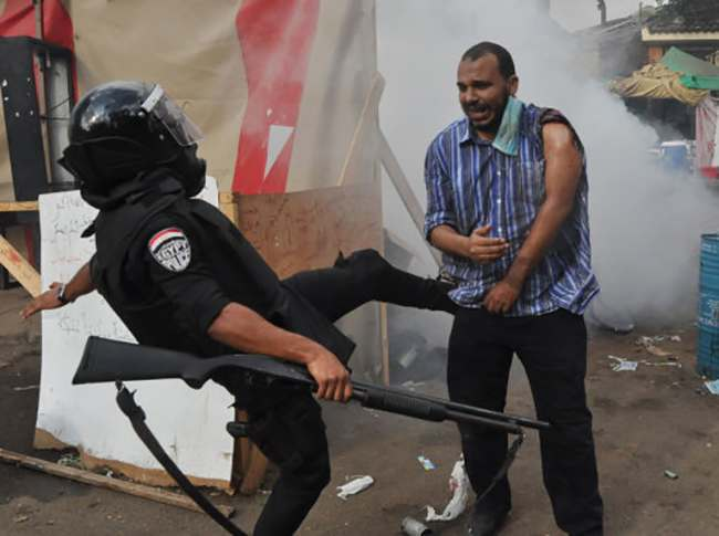 An Egyptian security force kicks a supporter of ousted Islamist President Mohammed Morsi as they clear a sit-in camp set up near Cairo University in Cairo's Giza district, Egypt, Wednesday, Aug. 14, 2013. Egyptian police in riot gear swept in with armored vehicles and bulldozers Wednesday to clear the sit-in camp and the other encampment set up by supporters of the country's ousted Islamist president in Cairo, showering protesters with tear gas as the sound of gunfire rang out. (AP Photo/Hussein Tallal)