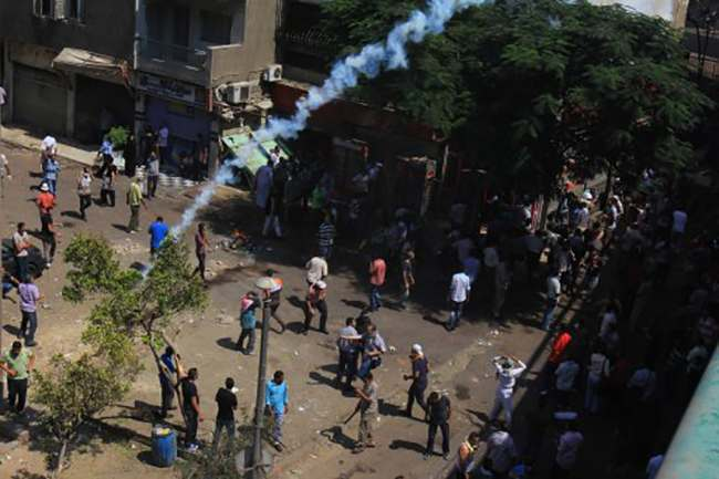 Supporters of Egypt's ousted President Mohammed Morsi clash with security forces near the largest sit-in by supporters of Morsi in the eastern Nasr City district of Cairo, Egypt, Wednesday, Aug. 14, 2013. Egyptian police in riot gear swept in with armored vehicles and bulldozers Wednesday to clear the sit-in camps set up by supporters of the country's ousted Islamist president in Cairo, showering protesters with tear gas as the sound of gunfire rang out. (AP Photo/Mohammed Abu Zeid)
