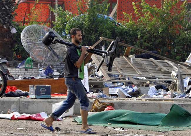 An Egyptian carries a fan he found among debris of a protest camp in Nahda Square, Giza, Cairo, Egypt, Thursday, Aug. 15, 2013. Egypt faced a new phase of uncertainty on Thursday after the bloodiest day since its Arab Spring began, with over 300 people reported killed and thousands injured as police smashed two protest camps of supporters of the deposed Islamist president. Wednesday's raids touched off day-long street violence that prompted the military-backed interim leaders to impose a state of emergency and curfew, and drew widespread condemnation from the Muslim world and the West, including the United States. (AP Photo/Amr Nabil)