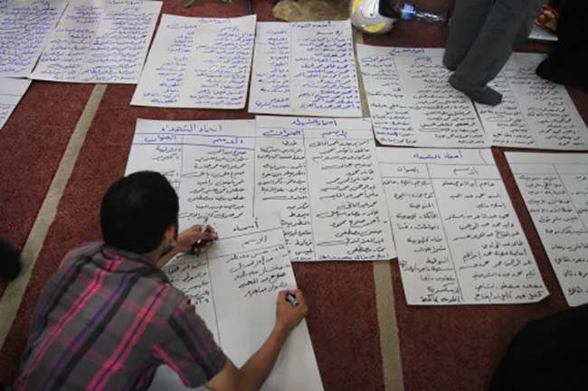 A man writes down identified names of bodies of supporters of ousted President Mohammed Morsi at the El-Iman mosque in Cairo's Nasr City, Egypt, Thursday, Aug. 15, 2013. Egyptian authorities on Thursday significantly raised the death toll from clashes the previous day between police and supporters of the ousted Islamist president, saying hundreds of people died and laying bare the extent of the violence that swept much of the country and prompted the government to declare a nationwide state of emergency and a nighttime curfew. (AP Photo/Ahmed Gomaa)