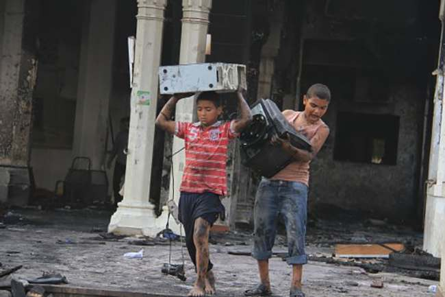 Egyptian children carry computer equipment in the burned remains of the Rabaah al-Adawiya mosque, in the center of the largest protest camp of supporters of ousted President Mohammed Morsi, that was cleared by security forces, in the district of Nasr City, Cairo, Egypt, Thursday, Aug. 15, 2013. The death toll keeps going up in Egypt after security forces swept through two sit-in sites yesterday, operated by supporters of Morsi. An Egyptian Health Ministry spokesman now says over 400 people died in the violence that has prompted international criticism. (AP Photo/Ahmed Gomaa)