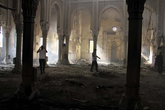 Egyptians walk among the burned remains of the Rabaah al-Adawiya mosque, in the center of the largest protest camp of supporters of ousted President Mohammed Morsi, that was cleared by security forces, in the district of Nasr City, Cairo, Egypt, Thursday, Aug. 15, 2013. The death toll keeps going up in Egypt after security forces swept through two sit-in sites yesterday, operated by supporters of Morsi. An Egyptian Health Ministry spokesman now says over 400 people died in the violence that has prompted international criticism. (AP Photo/Ahmed Gomaa)