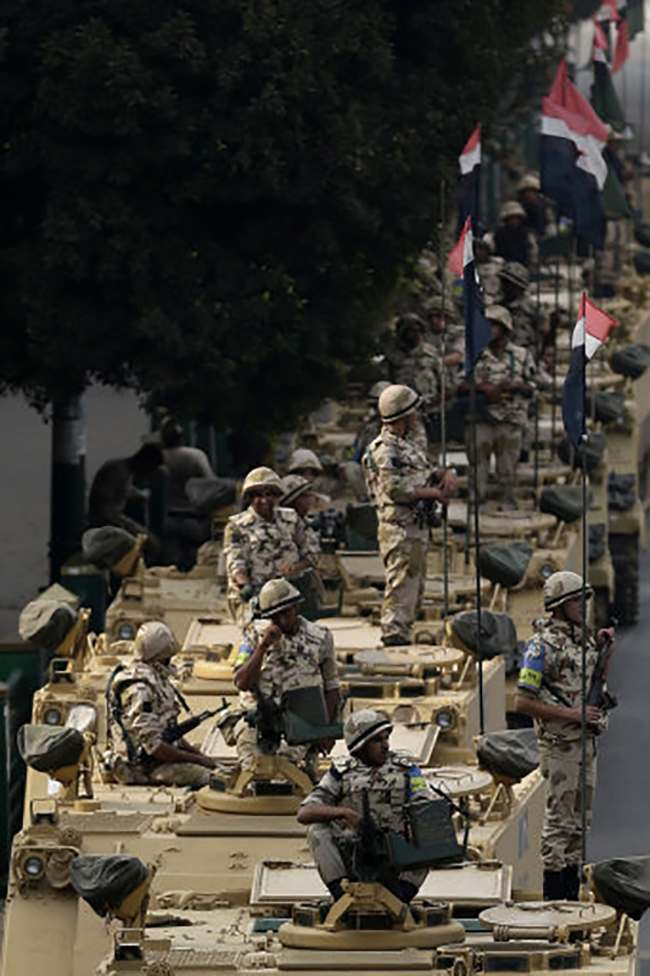 "Egyptian army soldiers take their positions on top and next to their armored vehicles while guarding an entrance to Tahrir square, in Cairo, Egypt, Friday, Aug. 16, 2013. Egypt is bracing for more violence after the Muslim Brotherhood called for nationwide marches after Friday prayers and a ""day of rage"" to denounce this week's unprecedented bloodshed in the security forces' assault on the supporters of the country's ousted Islamist president that left more than 600 dead. (AP Photo/Hassan Ammar)"