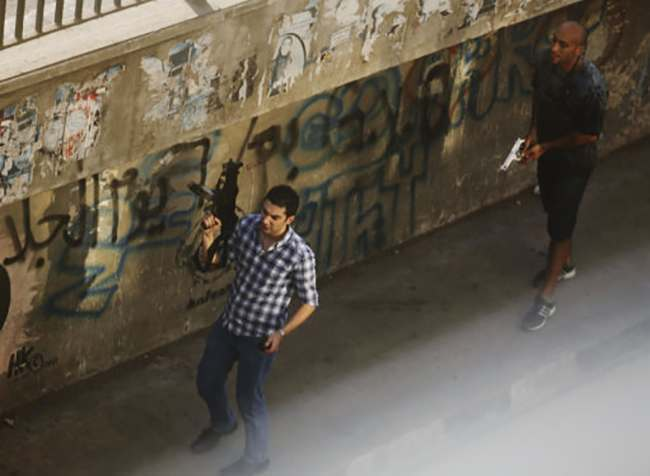 Two civilians holding guns walk on a street in the Zamalek neighborhood of Cairo, Egypt, Friday, Aug. 16, 2013. Gunfire rang out over a main Cairo overpass and police fired tear gas as clashes broke out after tens of thousands of Muslim Brotherhood supporters took to the streets Friday across Egypt in defiance of a military-imposed state of emergency following the country's bloodshed earlier this week. (AP Photo/Manoocher Deghati) WHITE CASTING AT LOWER RIGHT DUE TO WINDOW GLASS REFLECTION