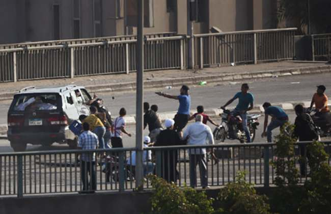 A supporter of ousted President Mohammed Morsi, center in blue, aims his gun at a car driver in Cairo, Egypt, Friday, Aug. 16, 2013. Egyptian security forces, backed by armored cars and bulldozers, moved on Wednesday to clear two sit-in camps by supporters of the country's ousted President Mohammed Morsi, showering protesters with tear gas as the sound of gunfire rang out at both sites. (AP Photo/Hassan Ammar)