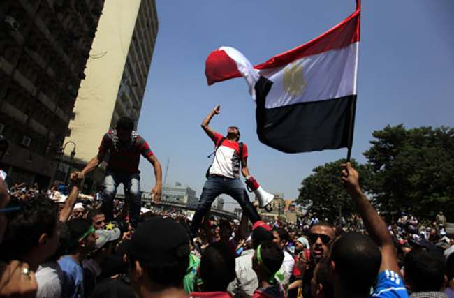 Supporters of Egypt's ousted President Mohammed Morsi chant slogans during a protest in Ramses Square in downtown Cairo, Egypt, Friday, Aug. 16, 2013. Heavy gunfire rang out Friday throughout Cairo as tens of thousands of Muslim Brotherhood supporters clashed with vigilante residents in the fiercest street battles to engulf the capital since the country's Arab Spring uprising. Tens of people were killed in the fighting nationwide, including police officers. (AP Photo/Khalil Hamra)
