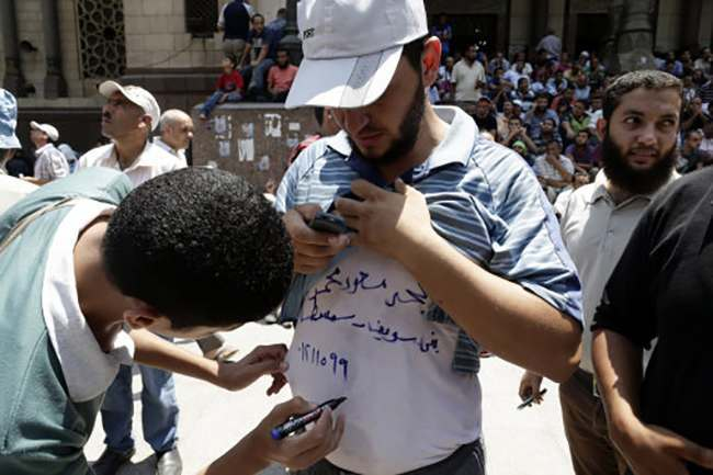"A supporter of Egypt's ousted President Mohammed Morsi writes his friend's name and address on his T-Shirt, in case he is injured or killed during clashes with Egyptian security forces and armed vigilantes, in Ramses Square, downtown Cairo, Egypt, Friday, Aug. 16, 2013. Heavy gunfire rang out Friday throughout Cairo as tens of thousands of Muslim Brotherhood supporters clashed with security forces and armed vigilantes in the fiercest street battles to engulf the capital since the country's Arab Spring uprising. Tens of people were killed in the fighting nationwide, including police officers. Arabic reads, "" Mohammad Massoud Mohammad, his home address and a phone number."" (AP Photo/Hassan Ammar)"