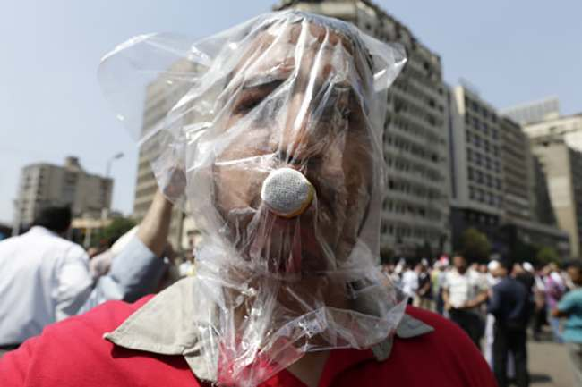 A supporter of Egypt's ousted President Mohammed Morsi poses with a homemade gas mask during clashes with Egyptian security forces in Ramses Square, downtown Cairo, Egypt, Friday, Aug. 16, 2013. Heavy gunfire rang out Friday throughout Cairo as tens of thousands of Muslim Brotherhood supporters clashed with security forces and armed vigilantes in the fiercest street battles to engulf the capital since the country's Arab Spring uprising. Tens of people were killed in the fighting nationwide, including police officers. (AP Photo/Hassan Ammar)