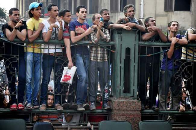 A group of Egyptians watch events outside the al-Fatah mosque, after hundreds of Muslim Brotherhood supporters barricaded themselves inside the mosque overnight, following a day of fierce street battles that left scores of people dead, near Ramses Square in downtown Cairo, Egypt, Saturday, Aug. 17, 2013. Authorities say police in Cairo are negotiating with people barricaded in a mosque and promising them safe passage if they leave. Muslim Brotherhood supporters of Egypt's ousted Islamist president are vowing to defy a state of emergency with new protests today, adding to the tension. (AP Photo/Hussein Tallal)