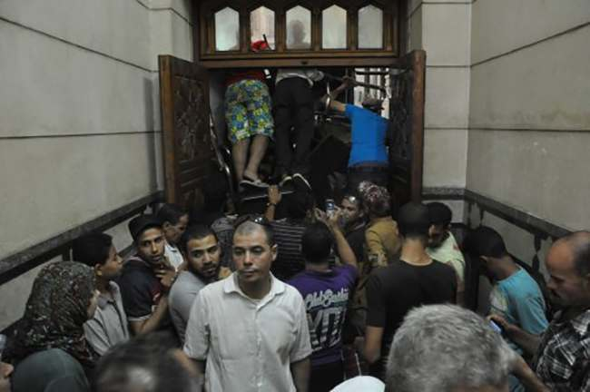 Pro-Muslim Brotherhood supporters shove furniture against the doors to stop anyone from breaking their way in the al-Fatah mosque, after hundreds of Islamist protesters barricaded themselves inside the mosque overnight, following a day of fierce street battles that left scores of people dead, near Ramses Square in downtown Cairo, Egypt, Saturday, Aug. 17, 2013. Authorities say police in Cairo are negotiating with people barricaded in a mosque and promising them safe passage if they leave. Muslim Brotherhood supporters of Egypt's ousted Islamist president are vowing to defy a state of emergency with new protests today, adding to the tension. (AP Photo/Hussein Tallal)