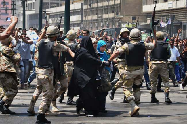 Egyptian security forces escort supporters of the Muslim Brotherhood, center, out of the al-Fatah mosque and through angry crowds, in the background, in Ramses Square, downtown Cairo, Egypt, Saturday, Aug. 17, 2013. Hundreds of Islamist protesters barricaded themselves inside the mosque overnight on Friday, following a day of fierce street battles. A Muslim cleric, Sheik Abdel-Hafiz el-Maslami, still inside the mosque told The Associated Press that people are afraid to leave the mosque out of fear of detention or being assaulted by the crowd outside. (AP Photo/Hussein Tallal)