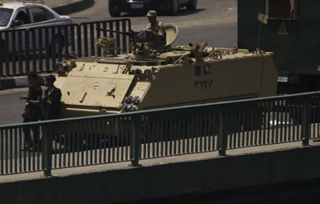 An Egyptian army armored vehicle is seen on a bridge over the Nile river at Zamalek District in Cairo, Egypt, Saturday, Aug. 17, 2013. Authorities say police in Cairo are negotiating with people barricaded in a mosque and promising them safe passage if they leave. Muslim Brotherhood supporters of Egypt's ousted Islamist president are vowing to defy a state of emergency with new protests today, adding to the tension. (AP Photo/Manu Brabo)