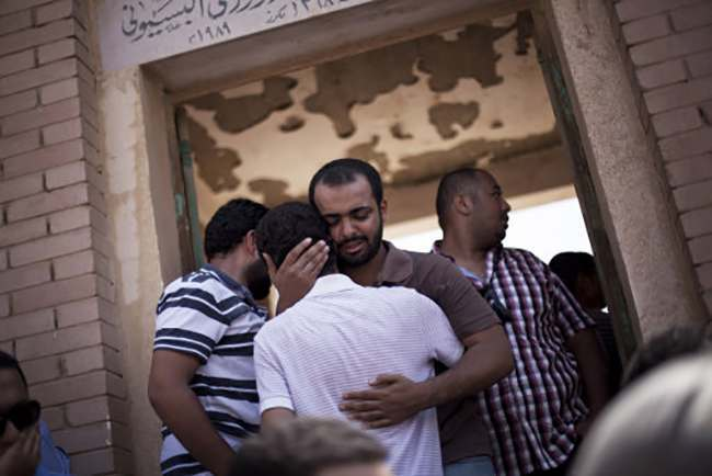 A friend of Ammar Badie, 38, killed by Egyptian security forces Friday during clashes in Ramses Square, and also son of Muslim Brotherhood's spiritual leader Mohammed Badie, comforts a relative while attending his burial in Cairo's Katameya district, Egypt, Sunday, Aug. 18, 2013. Egypt increased security at the Supreme Constitutional Court building ahead of planned mass rallies by supporters of the country's ousted President Mohammed Morsi. (AP Photo/Manu Brabo)
