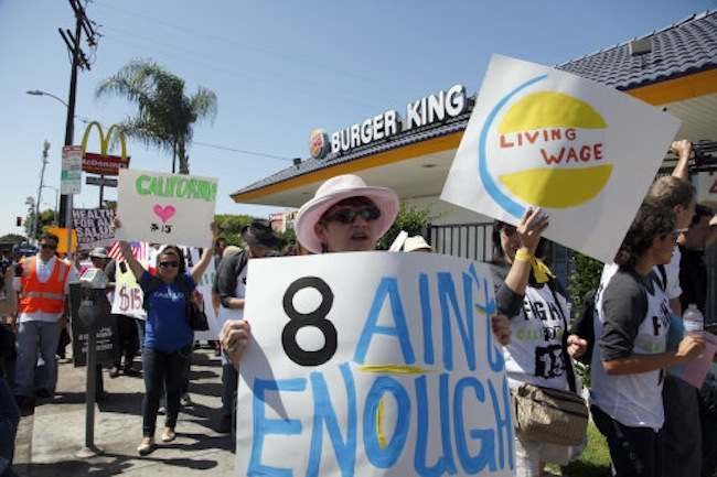 Protestors demonstrate outside a fast food restaurant on Thursday, Aug. 29, 2013, in Los Angeles. Fast-food protests were under way Thursday in U.S. cities including New York, Chicago and Detroit, with organizers expecting the biggest national walkouts yet in a demand for higher wages. (AP Photo/Nick Ut)