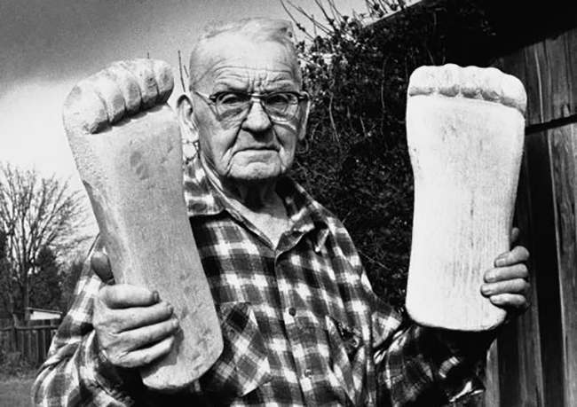 Rant Mullens, 86, shows off one of several pair of wooden feet he has whittled since 1928, April 12, 1982, Vancouver, Wa. Mullens says the feet have figured in Bigfoot foot print sightings in the Northwest. (AP Photo)