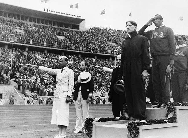 The ceremony honoring the three winners in the 100 meter Olympic final in Berlin on August 3, 1936, which was won by Jessie Owens, U.S.A, middle, second was Tinus Osendarp, Holland, front, and third Ralph Metcalf, U.S.A. (extreme right). (AP Photo)
