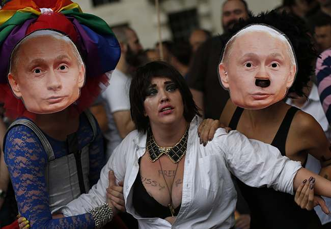 "Activists stage a theatrical play where gay people are restrained by others wearing masks depicting Russian President Vladimir Putin, during a protest against Russia's new law on gays, in central London, Saturday, Aug. 10, 2013. Hundreds of protesters, called for the Winter 2014 Olympic Games to be taken away from Sochi, Russia, because of a new Russian law that bans ""propaganda of nontraditional sexual relations"" and imposes fines on those holding gay pride rallies. (AP Photo/Lefteris Pitarakis)"
