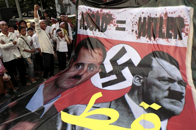 Indonesian Muslims display a banner comparing Syrian President Bashar Assad with Nazi dictator Adolf Hitler during a rally calling for an end to the violence against fellow Muslims in Syria and Rakhine state of Myanmar, in Jakarta, Indonesia, Sunday, Aug. 12, 2012. (AP Photo/Dita Alangkara)