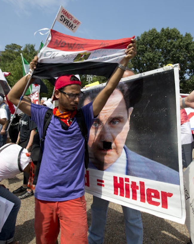 A man calling for military action in Syria, holding a sign with the image of Syrian President Bashar Assad as Hitler is blocked by another man who is against military action in Syria in front of the White House, Saturday, Aug. 31, 2013, in Washington. (AP Photo/Carolyn Kaster)