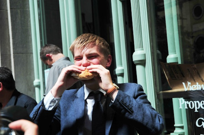 "CityAM reporter Jim Waterson tucks into a fried egg roll, cooked in intense sunlight on Eastcheap Central London.  Moments before this shot, Waterson's heair was smoldering in the heat. The effect is caused by nearby building 20 Fenchurch Street - commonly known at ""The Walkie-Talkie"" - focussing sunlight.  These images were taken a day after parts of a Jaguar car  melted whilst parked on Eastcheap."