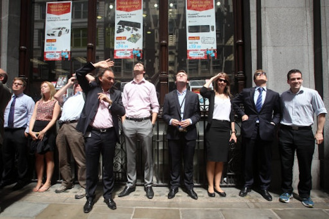 "People shield their eyes as sunlight is reflected off the ""Walkie Talkie"" skyscraper at 20 Fenchurch Street in central London."