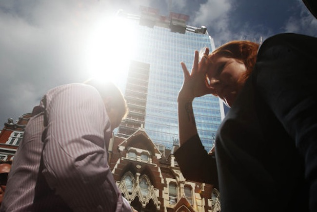 "A woman shields her eyes as sunlight is reflected off the ""Walkie Talkie"" skyscraper at 20 Fenchurch Street in central London."