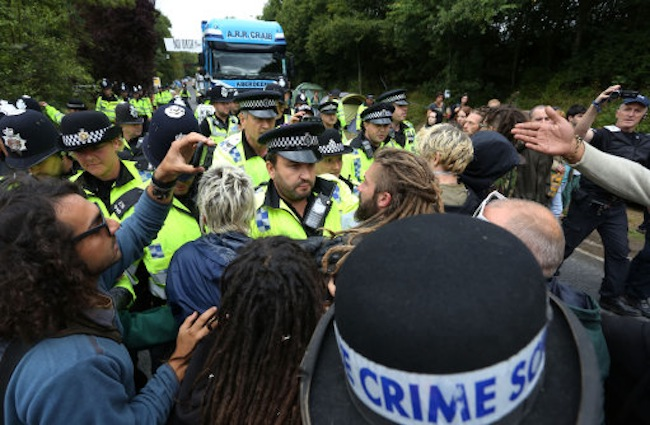 Police officers push back environmental activists as they slow down a lorry heading to the Cuadrilla exploratory drilling site in Balcombe, West Sussex, as anti fracking demonstrations continue.