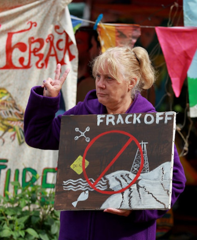 An environmental activist airs her views outside the Cuadrilla exploratory drilling site in Balcombe, West Sussex, as anti fracking demonstrations continue.