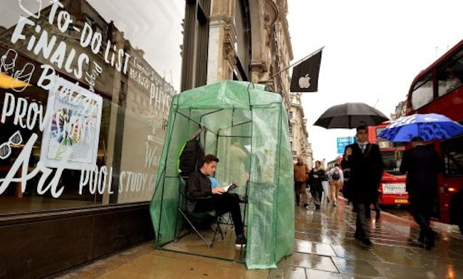 Gad Harari aged 17, from London, sits in his plastic greenhouse which is the only shelter for himself as he waits to buy the new iPhone in Regent Street central London, which goes on sale in the UK this coming Friday.