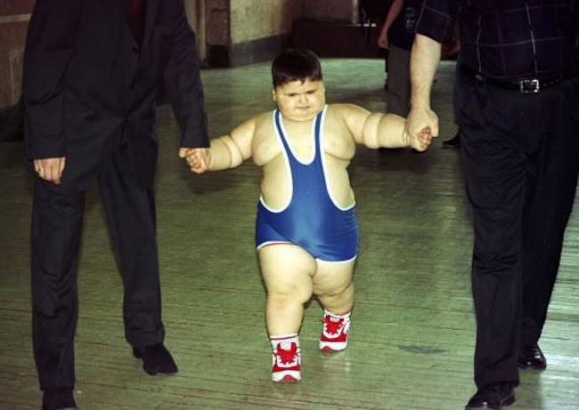 Young wrestler Dzhambulat Khotokhov, a 4-year-old Russian weighing 56 kilograms (123 pounds) with a height of 118 centimeters (3 feet 11 inches) is escorted to wrestle against Georgy Bibilauri, a Georgian, who turned 5 on Wednesday, 120 centimeters (4 feet) tall and weighs 51 kilograms (112 pounds), Tbilisi, Wednesday, July 9, 2003. Wrestlers Georgy Bibilauri and Dzhambulat Khotokhov had both hoped for victory, but they settled for ice cream instead. After the boys tied on the mat, they went off to celebrate Bibilauri's birthday with ice cream and chocolate. (AP Photo/ Shakh Aivazov)