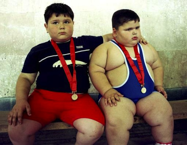 Young wrestlers Dzhambulat Khotokhov, a 4-year-old Russian weighing 56 kilograms (123 pounds) with a height of 118 centimeters (3 feet 11 inches), right, and Georgy Bibilauri, a Georgian, who turned 5 on Wednesday, 120 centimeters (4 feet) tall and weighing 51 kilograms (112 pounds) rest after wrestling, Tbilisi, Wednesday, July 9, 2003. Wrestlers Georgy Bibilauri and Dzhambulat Khotokhov had both hoped for victory, but they settled for ice cream instead. After the boys tied on the mat, they went off to celebrate Bibilauri's birthday with ice cream and chocolate. (AP Photo/Shakh Aivazov)