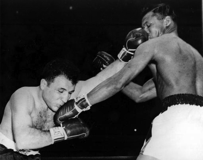 Jake LaMotta, left, and challenger Sugar Ray Robinson exchange lefts to the face in first round of their middleweight championship bout at Chicago Stadium, Chicago, Ill., Feb. 14, 1951. Robinson wrested the crown from LaMotta with a technical knockout in the 13th round. (AP Photo)