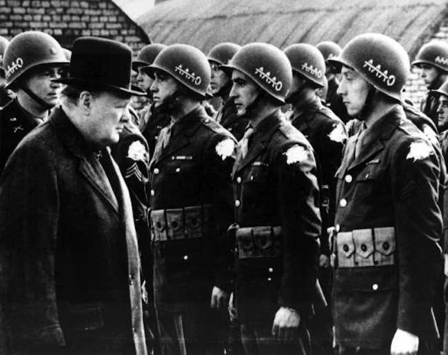 """British Prime Minister Winston Churchill, left, reviews American troops at a base in England on the eve of D-Day, June 1944, during World War II. The initials AAAO on the steel helmets with a line across the As stands for """"Anywhere, Anytime, Anyhow, Bar Nothing."""" The identification shoulder patches of the G.I.s are blotted out by the censor. (AP Photo)"""