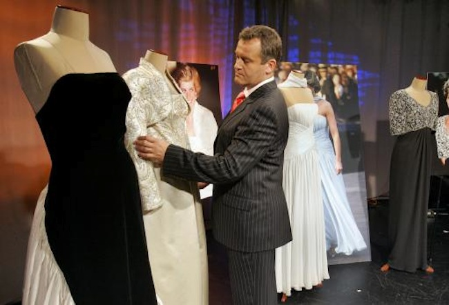 "Paul Burrell, Princess Diana's former butler, looks at a long, formal dinner dress in oyster duchesse satin, with a bolero jacket by Victor Edelstein that belonged to the Princess of Wales, in New York Monday Aug. 13, 2007. At left is the dress, valued at over $300,000 that is being offered on eBay through August 22, with proceeds going to the America's Promise charity which raises money for disadvantaged children. Burrell is returning as a judge for the second season of the WE cable television channel reality series ""American Princess."" At left is a positive negative black and white evening dress and bolero jacket by Murray Arbeid, second left is a long, formal dinner dress in oyster duchesse satin, with a bolero jacket by Victor Edelstein and at right is a long evening dress of back silk crepe and diamante paste embroidery by Catherine Walker, both of which also belonged to Princess Diana. (AP Photo/Richard Drew)"