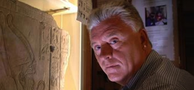 Medium and psychic Derek Acorah examines hieroglyphics on a stone tableau at the Petrie Museum of Egyptian Archaeology in central London.