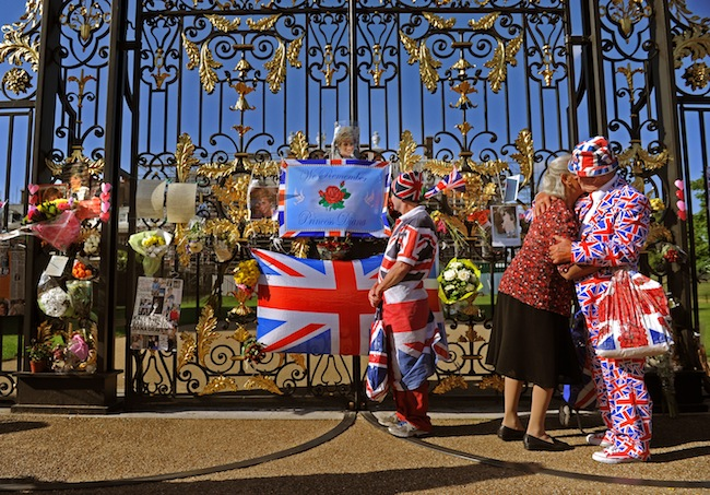 John Loughrey (centre) looks at tributes left outside Kensington Palace, London, as a couple embrace, on the anniversary of the death of Diana, Princess of Wales, who was killed in a car crash in central Paris along with Dodi Fayed.