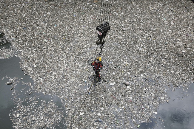In this photo taken Tuesday, July 20, 2010, Mexican sewer diver Julio Camara stands on a cage as he is going down for a dive at the city's drainage system plant, on the outskirts of Mexico City. Camara, who makes less than US $ 500 a month diving in the city's sewage system clearing blockages and repairing infrastructure, says he is the only sewage diver in the Mexican capital, from where at least 1000 tons of rubbish are extracted per month, according to Alejandro Martinez, Mexico City's water system operator. (AP Photo/Carlos Jasso)
