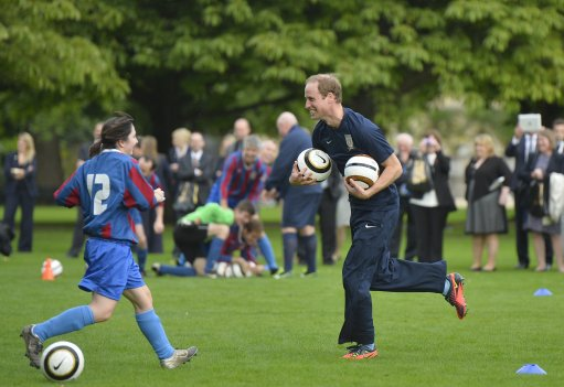 The Duke of Cambridge trains with members of the Royal household, during the second half of a match between the Polytechnic FC and the Civil Service FC, in the grounds of Buckingham Palace's garden, central London.