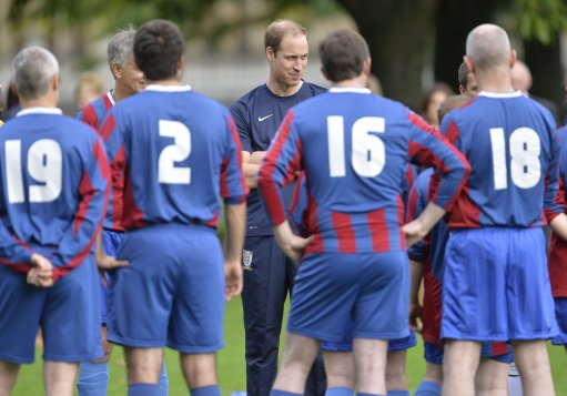 The Duke of Cambridge (centre) speaks with members of Polytechnic FC prior to their match against the Civil Service FC, in the grounds of Buckingham Palace's garden, central London.