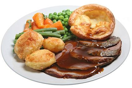 Traditional Sunday roast beef dinner with Yorkshire pudding, roast potatoes and vegetables