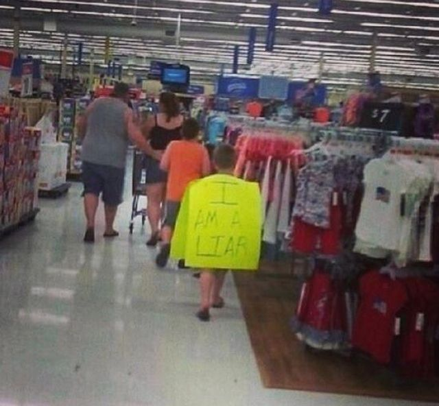 "kid wearing ""I AM A LIAR"" sign."