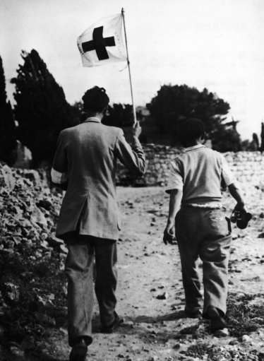 Swiss Jean Courvoisier, staff member of the Red Cross in Jerusalem, holds his organization's flag as he walks together with an unidentified colleague on no man's land in search for victims of the Jewish Arab conflict on May 10, 1948 in the Katamon outskirts of Jerusalem, Israel. Despite of the flag he was shot on twice by Arab snipers.