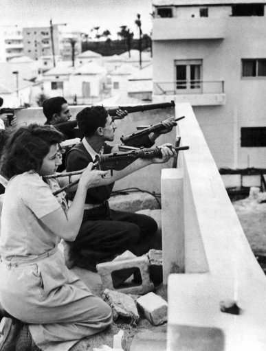 Members of the Jewish right-wing underground organization Irgun Zvai Leumi (National Military Organization in the Land of Israel) are armed with rifles, revolvers and automatic weapons as they take position on the rooftop of a Jewish house in case of Arab attack on the Jaffa - Tel Aviv border in the Manshiah Jewish quarter in Tel Aviv, Israel, on December 27, 1947. The Zionist guerrilla force began an armed revolt against British rule in Palestine.