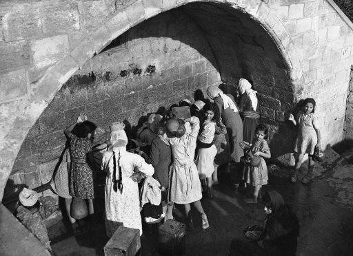 Arab women and children draw water from Mary' well in Nazareth, Israel on Dec. 7, 1946, the ancient spring which legend relates supplies water for Mary. Joseph and Jesus.