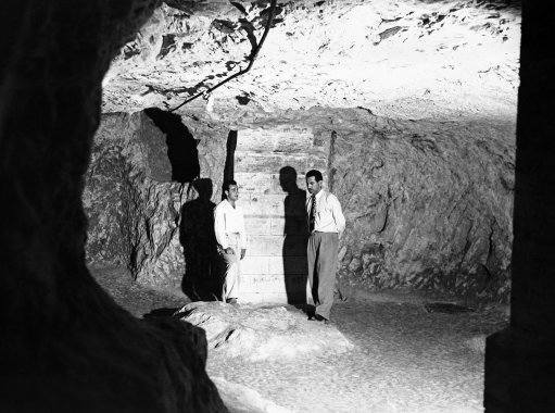 A view inside the Grotto, believed to be the cave in which Joseph and Mary Dwelt. A guide, left, relates the legend to a tourist as they stand by the remains of a stone table on Dec. 7, 1946 in Israel. The Grotto is situated beneath the modern Franciscan Church of St. Joseph's, Nazareth.